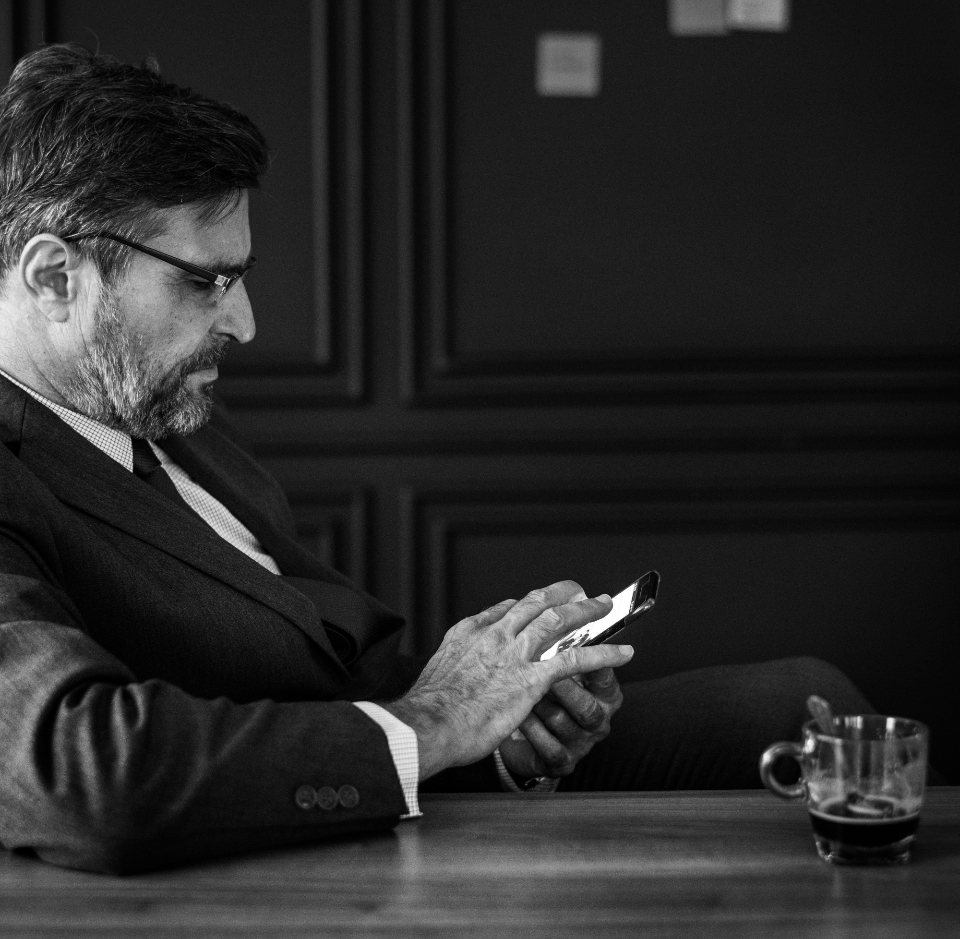 american black and white boss break time business businessman bw caucasian checking coffee coffee break dark device digital european gray scale grayscale guy hand having holding internet latin latino looking man manager