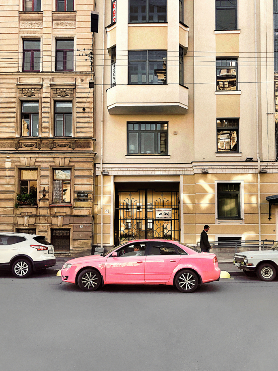 pink car street city building road travel transport person move automobile