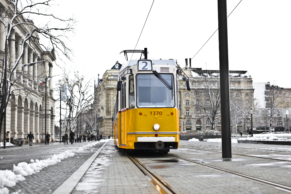 yellow city tram cold snow transport pole building electric vintage old tram lines track train