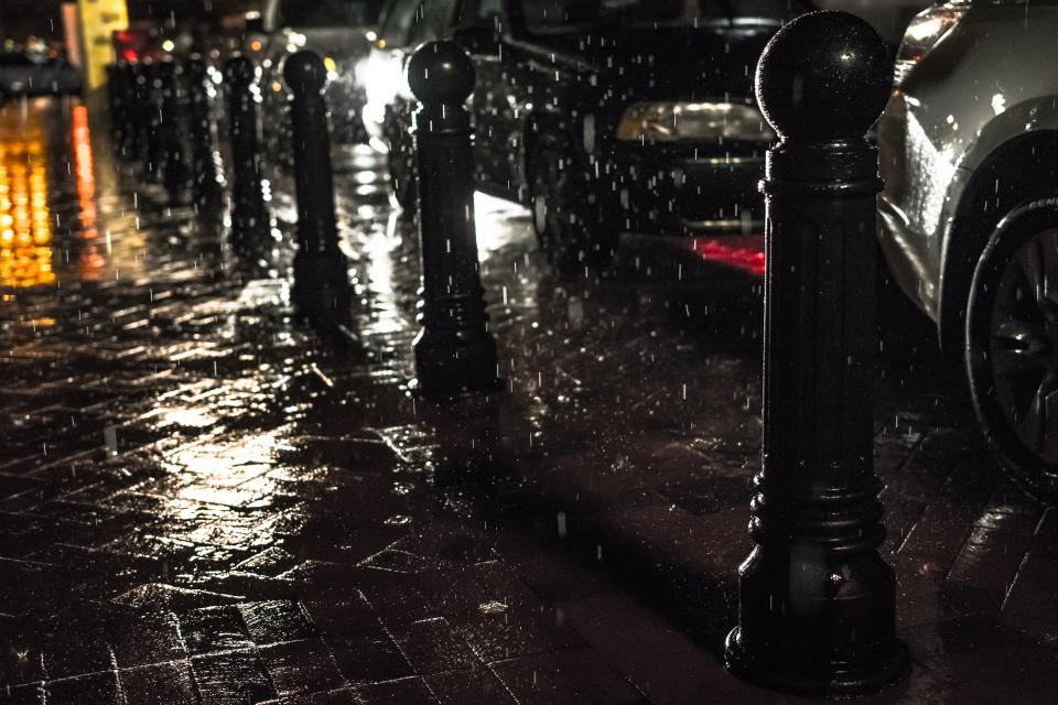 still items things sidewalk pavement posts traffic cars vehicles rain downpour wet water reflection city metro streets urban downtown
