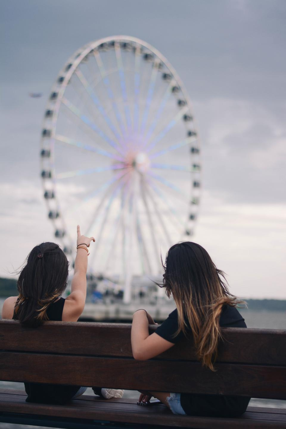 women girls ladies people friends bonding ferris wheel them amusement park point sit bench nature sky clouds bokeh