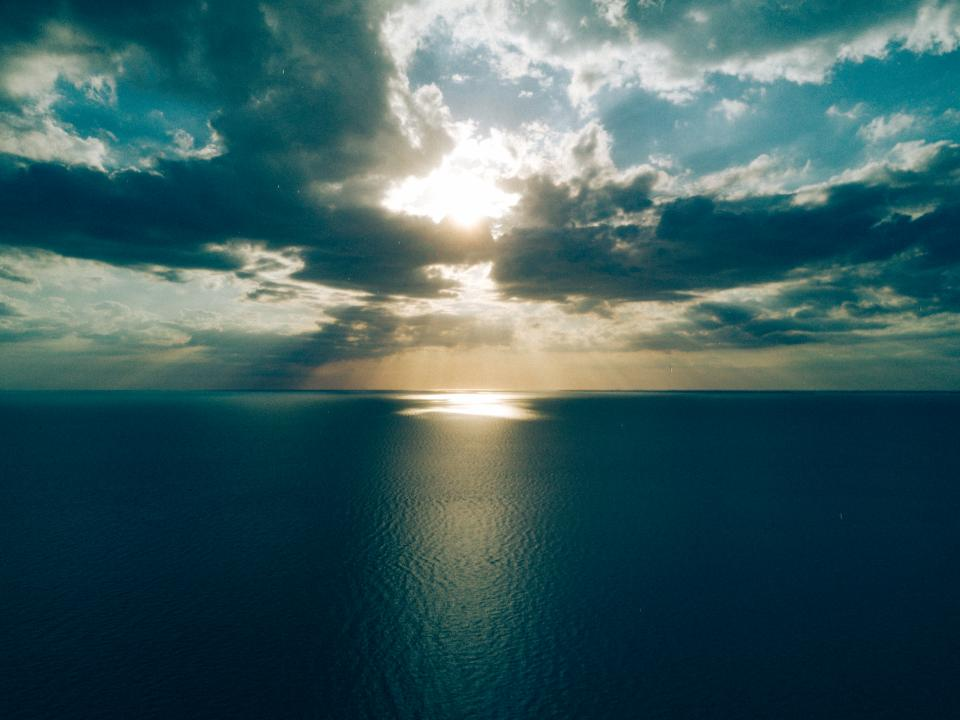 sea ocean blue water nature sunlight horizon cloudy sky dark clouds