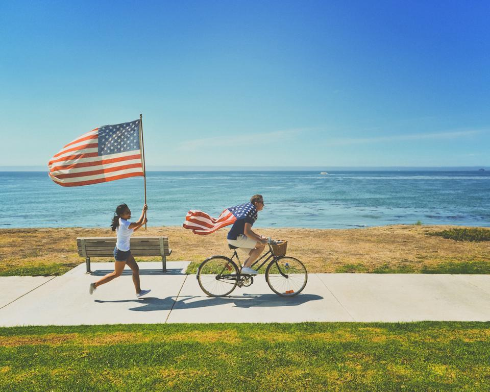 bicycle couple happy sweet happy american flag grass bench beach summer sky clouds