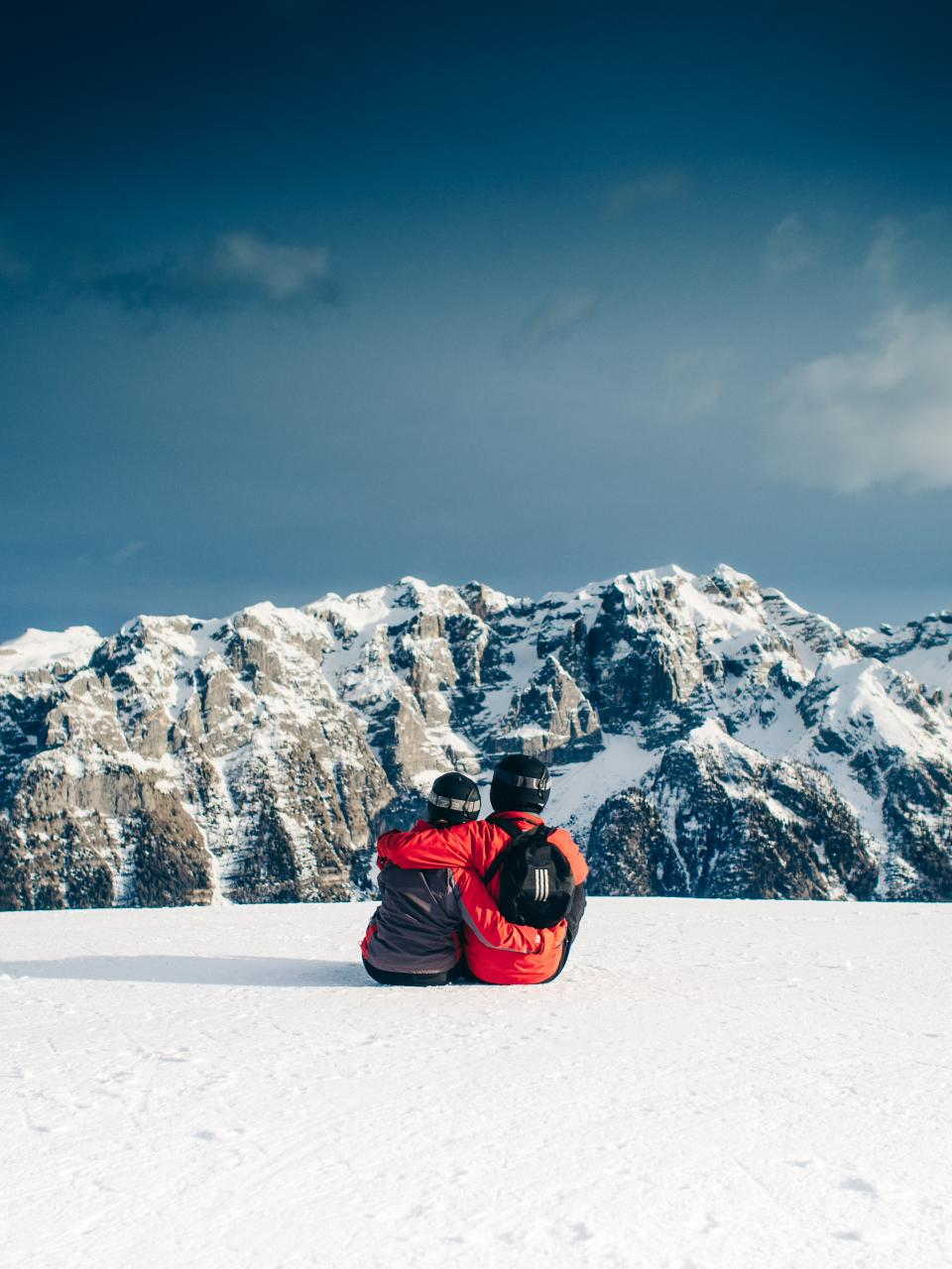 skiing snowboarding couple love romance hugging snow mountains peaks sky outdoors nature landscape