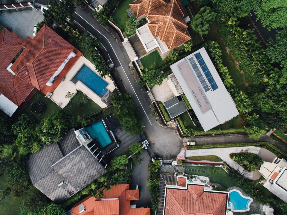 architecture building infrastructure houses village green grass trees plant nature swimming pool rooftops aerial view