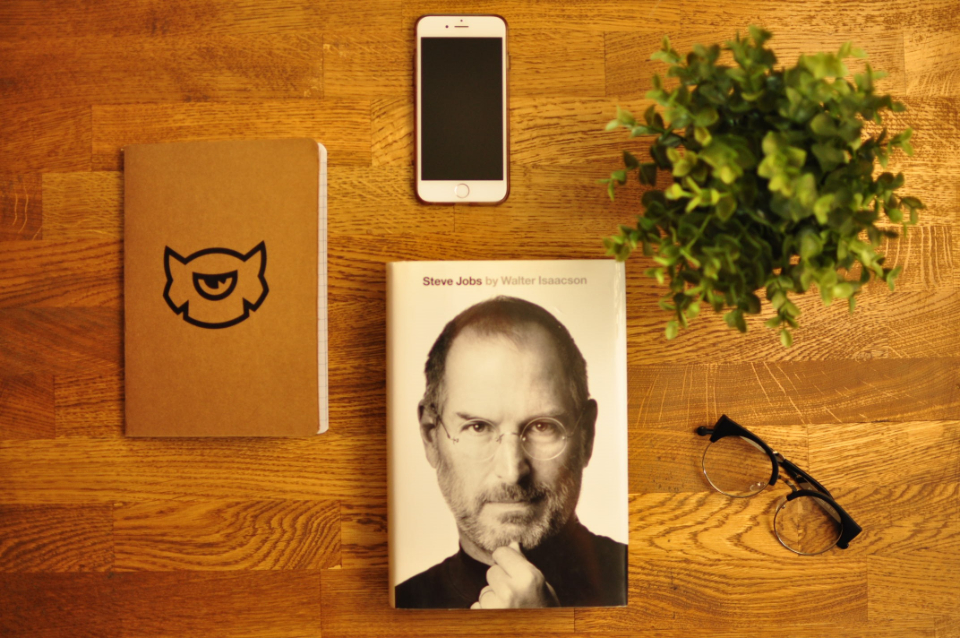 apple iphone workplace books table steve jobs book wood desk office business plant glasses notepad notebook