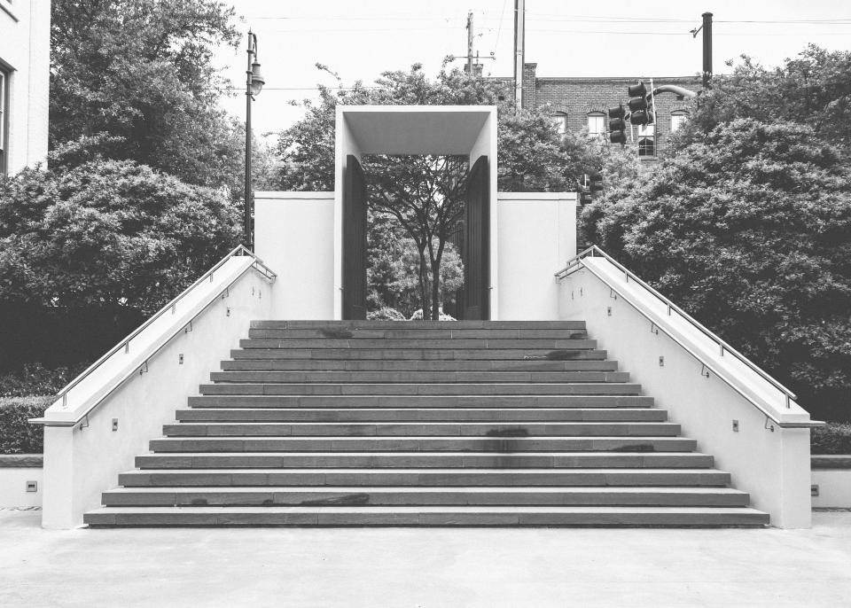 steps railing gate entrance city trees black and white