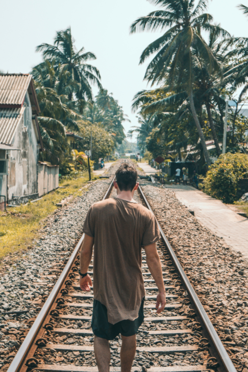 man walking tracks train transport alone summer vacation holiday travel palm tree house building