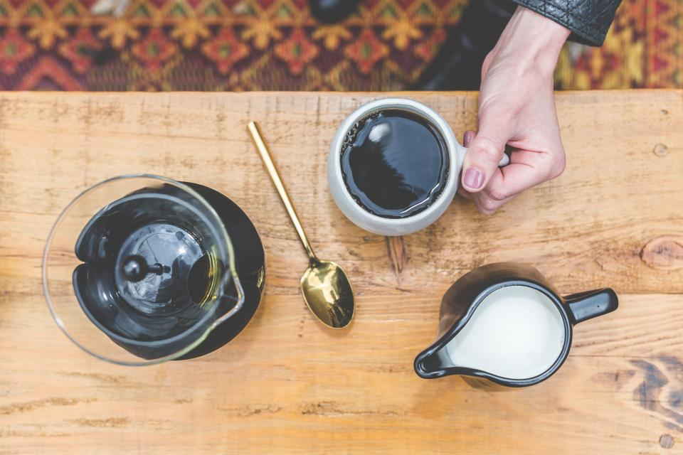 black brewed coffee milk hot cold drink cup spoon coffeehouse cafe shop wooden table hand manicure