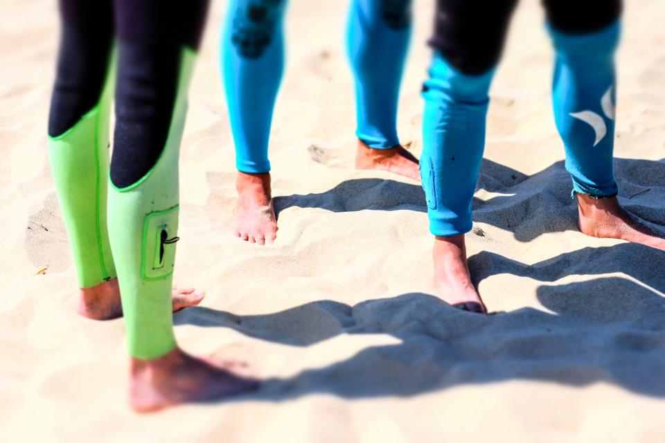 foot legs people beach white sand wetsuit summer outdoor sunny day shadow