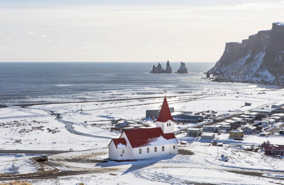 snow winter church building structure sea water clouds sky horizon cliff rocks hill houses sunny day landscape nature