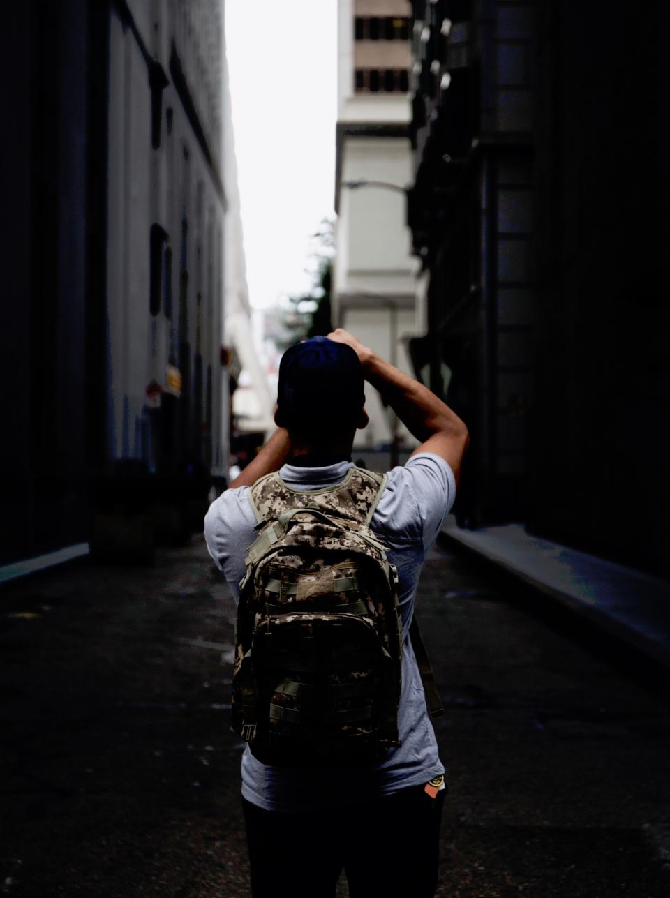 street alley people man guy photographer backpack