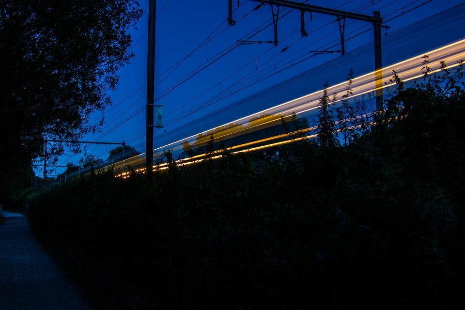 long exposure car transportation photography dark night city urban lights highway road trees cable wires train blue sky