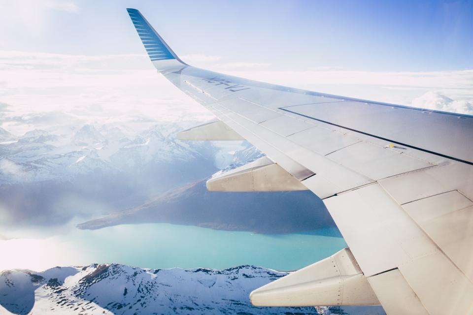 airplane airline travel trip clouds blue sky flight mountain landscape nature sea water snow winter