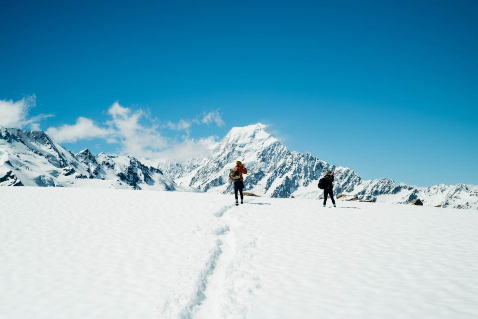 people man woman lady guy couple travel trip adventure camera photo photographer record bag pack snow white mountain sky blue clouds winter mountain climber