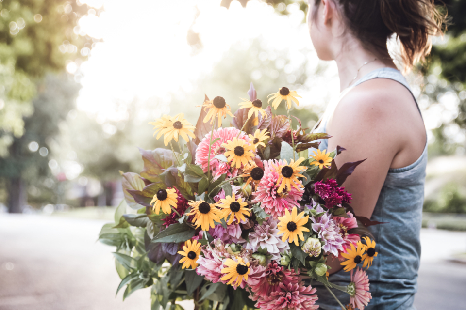 woman holding bouquet flowers girl sunshine female hair arm skin outside bokeh copyspace florist fresh floral gift delivery
