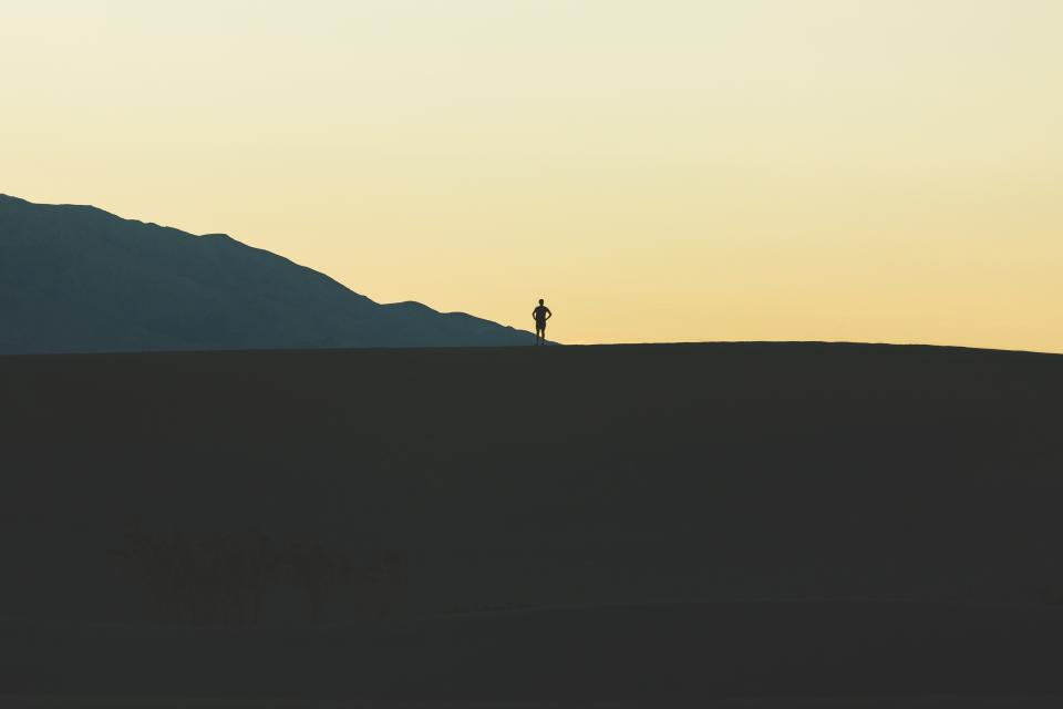 nature landscape mountains slope summit peaks sky horizon guy man male people stand trek hike climb silhouette shadows black yellow