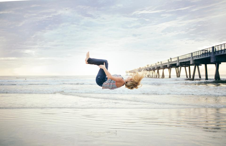 sea ocean water waves bridge structure people girl tumbling beach shore coast