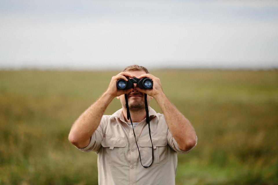 people man binoculars green nature landscape grass