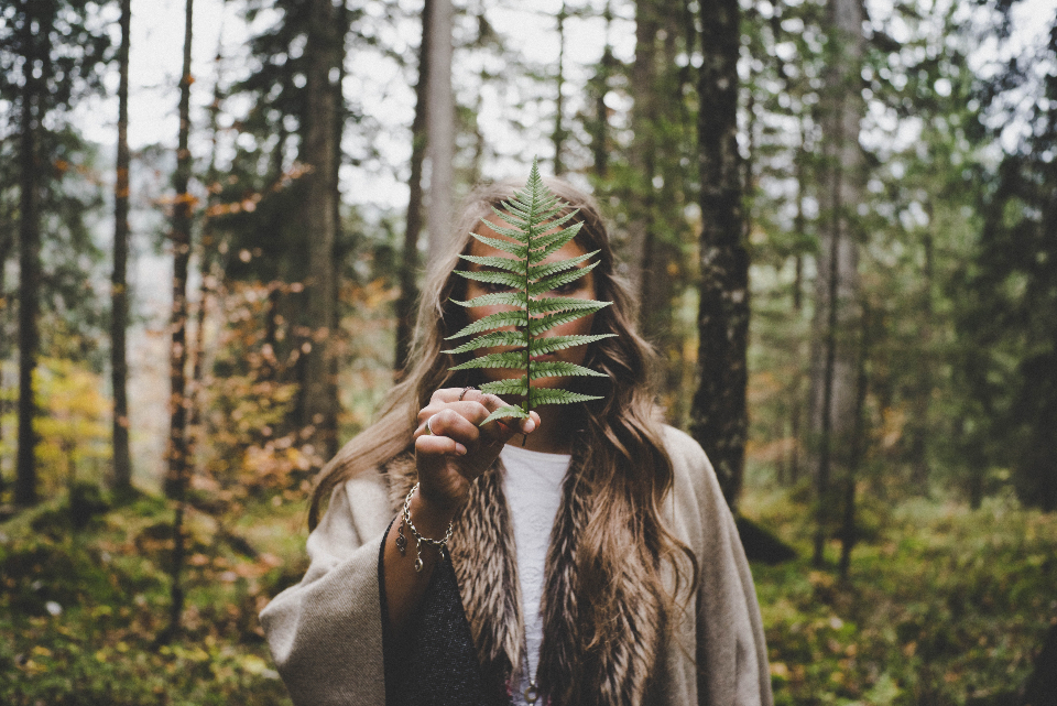 woman hiding leaf tree adventure trail forest woods female girl attractive hand hold