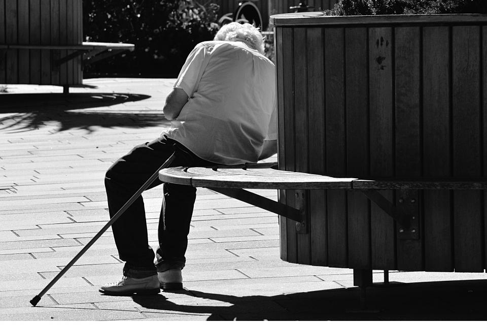 people man old setting bench chair garden park plants black and white cane shadow