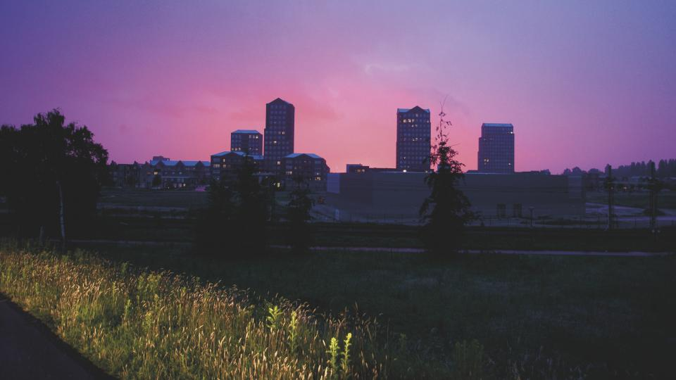 urban city establishment building structure infrastructure tower clouds sky pink grass plant