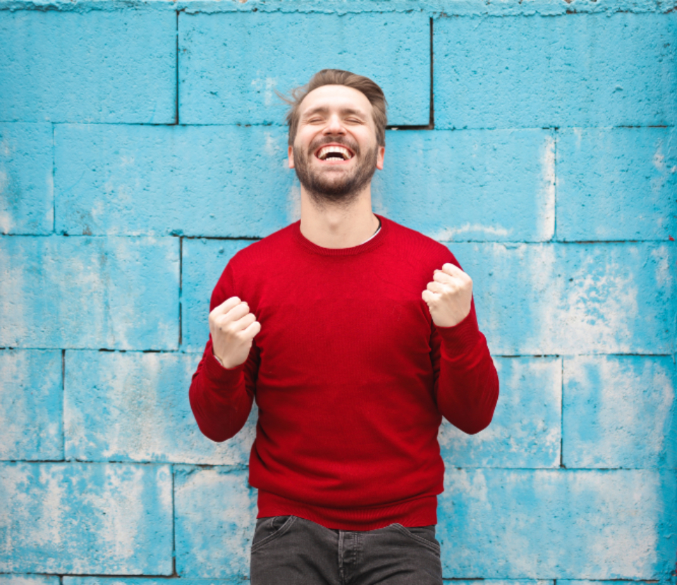 man celebrating smile happy beard fist pump fists blue brink wall red jumper jersey jeans fashion male people