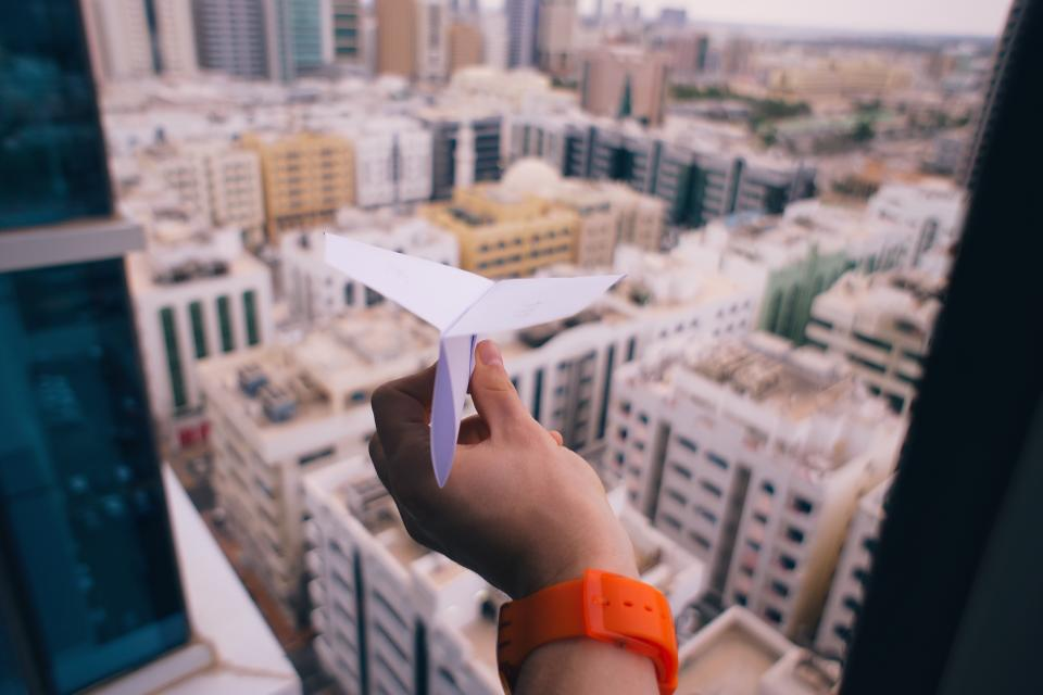 paper airplane hand building watch window architecture infrastructure city towers urban art folding blur