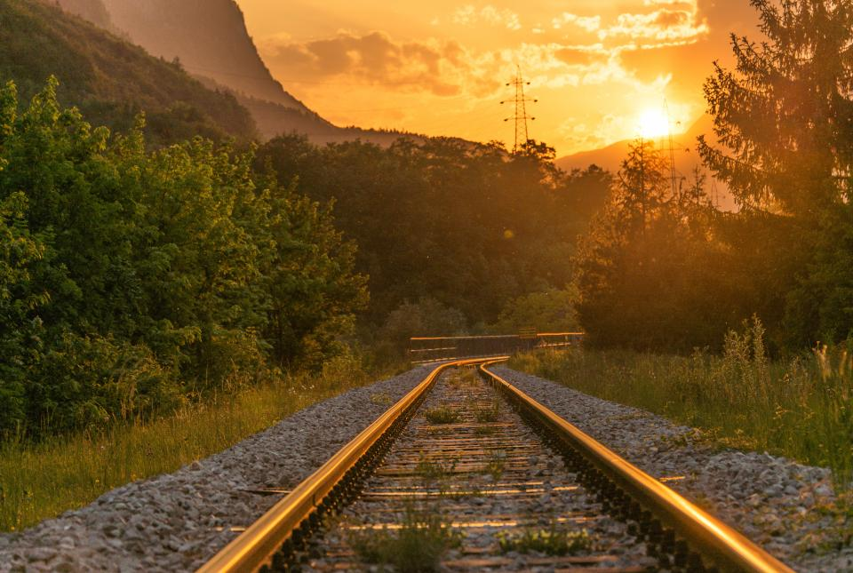 trail train station rail steel rocks forest woods trees grass sunset clouds sky mountain