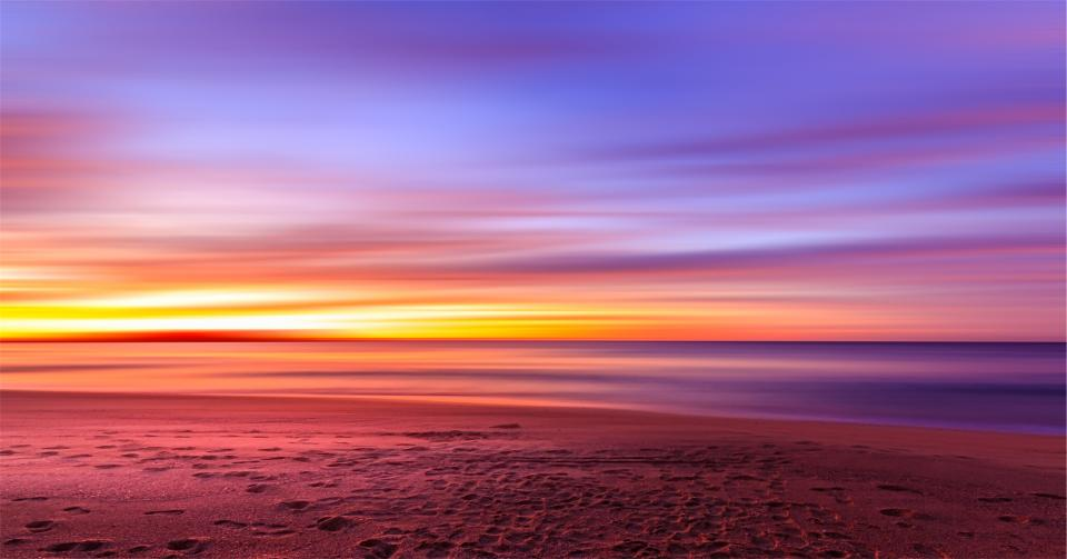sunset purple sky beach sand footprints shore water ocean sea horizon