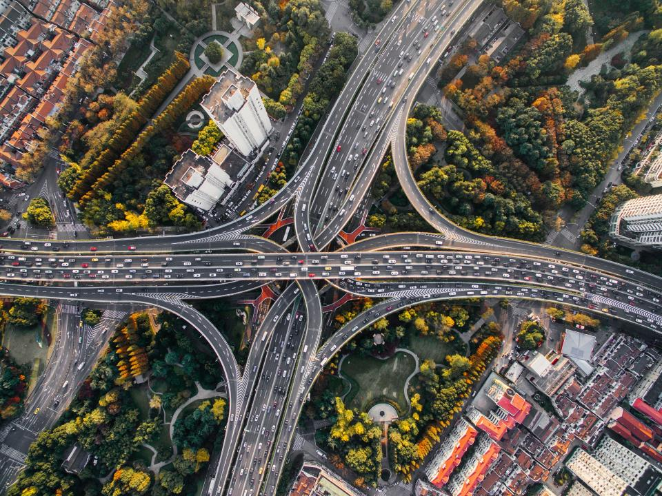 architecture buildings infrastructure aerial view rooftops city road highway car transportation vehicle travel trees plant nature