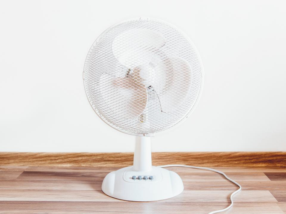 white fan objects hardwood floor wall