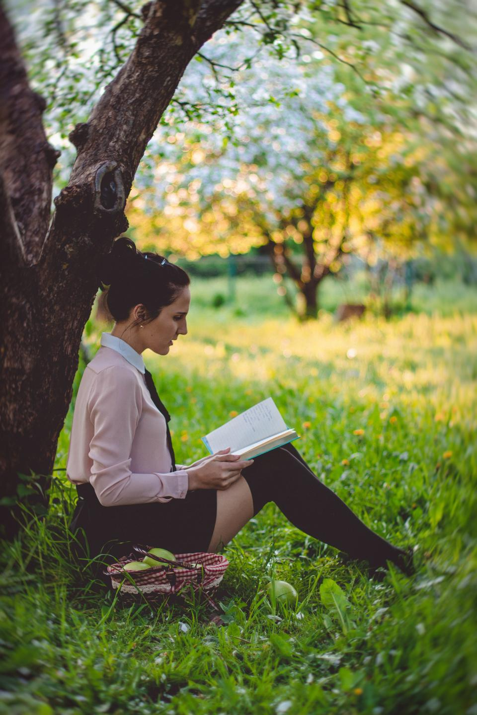 people girl woman sitting reading book alone fashion clothing nature plant tree outdoor green grass petal travel blur bokeh basket fruit food