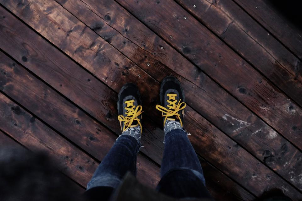 shoes yellow laces wood floor