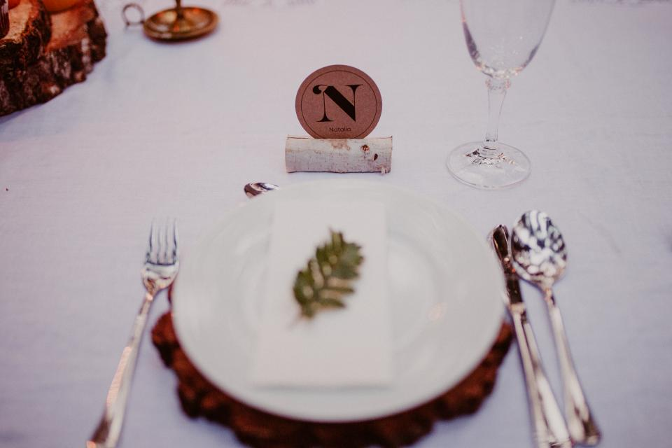 events venue banquet hall wedding party plate spread styling cutlery utensils fern leaves monogram glass still bokeh