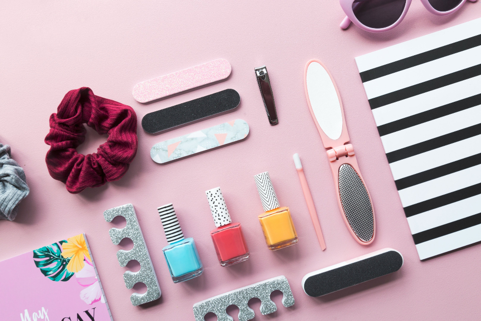 background fashion cosmetics products girl nail polish lifestyle accessories file hair tie feminine flat lay stationery desk pink