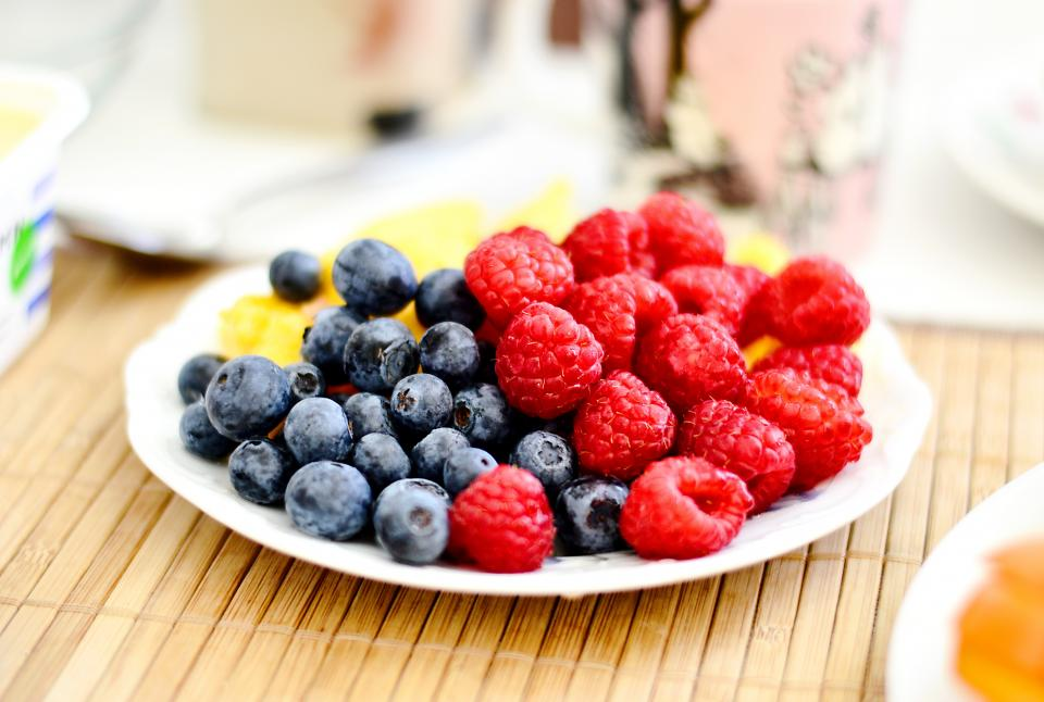 food eat fruits berries raspberries blueberries wood table mat spread plates