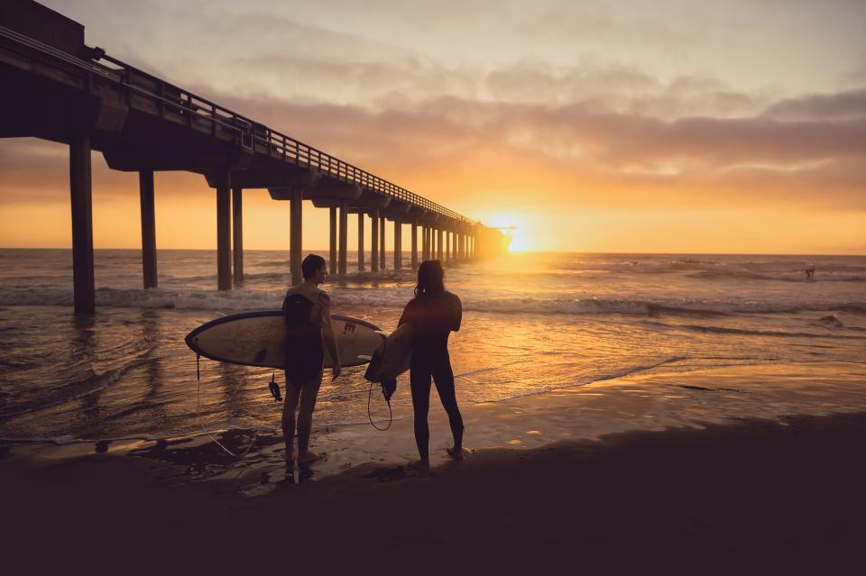 people man woman surfer surfing sea ocean water beach shore coast bridge structure sky clouds sunset sunrise sunlight