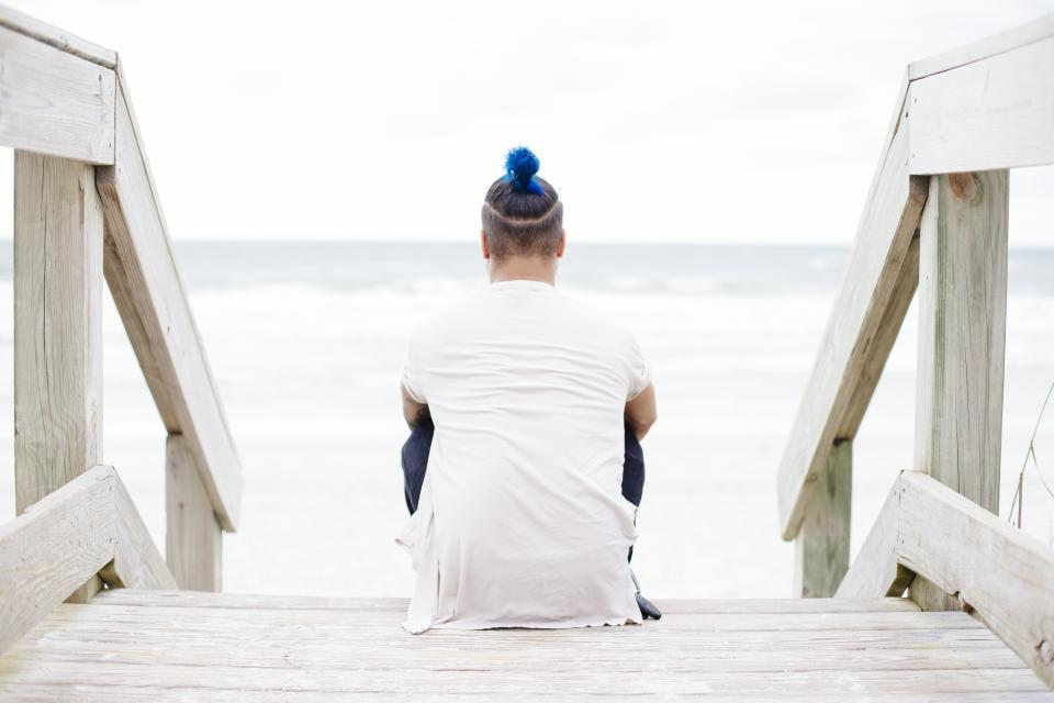 guy man male people back contemplate sit fashion style blue hair stairs wood view beach shore sand water ocean sea waves white