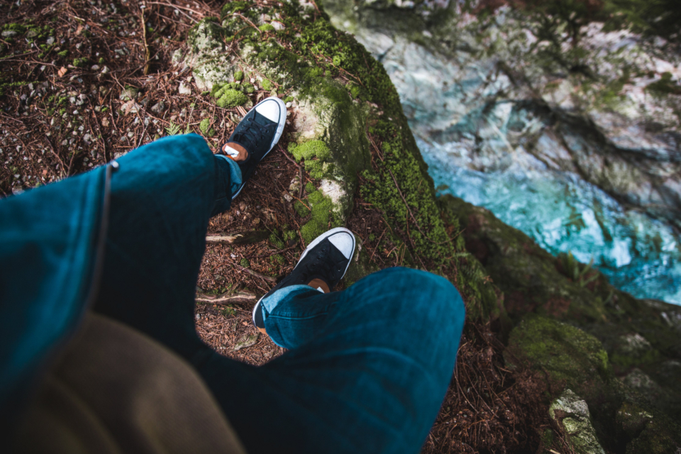 shoes steep cliff nature hiking adventure river rocks outdoors person youth feet looking down