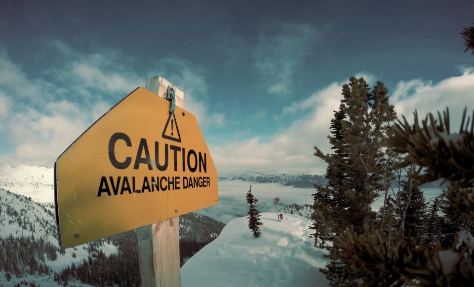 nature landscape mountains summit peaks snow forests trees sky clouds sign caution danger yellow blue white