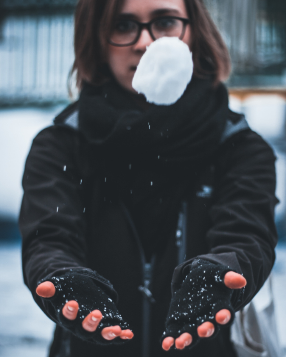 woman catching snowball cold frozen ice snow people person glasses female girl gloves jacket white black