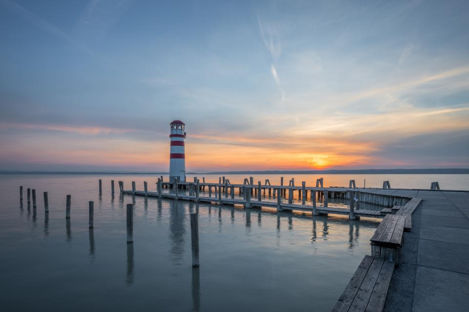 pier dock ocean sea water sunset dusk lighthouse sky clouds nature landscape