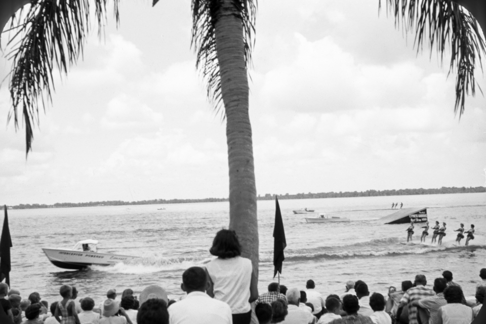 water skiing lake women retro fun group performers beach boat tree film photography vintage female audience