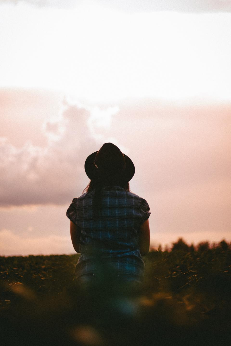 people woman checkered grass sunset alone clouds sky hat