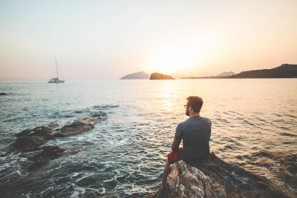 guy man people sunset dusk sailboat ocean sea water rocks shore landscape nature horizon mountains view looking
