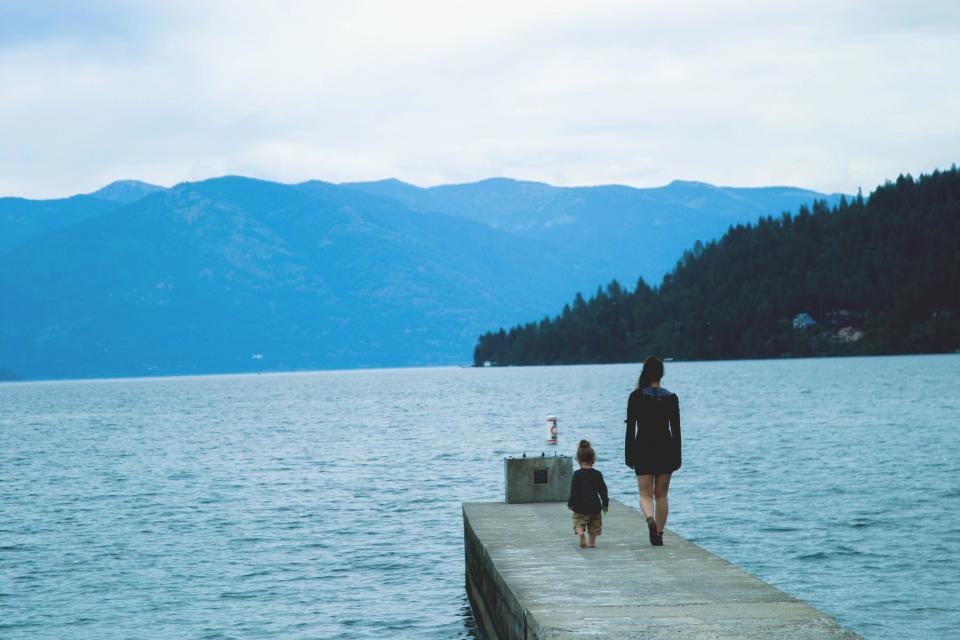 dock lake water girl woman child kid mother family people mountains trees forest hills nature landscape outdoors