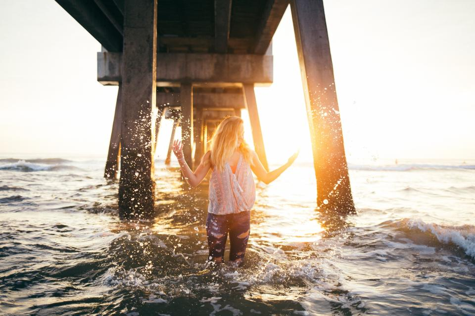 sea ocean water waves bridge structure people girl sunrise sunset