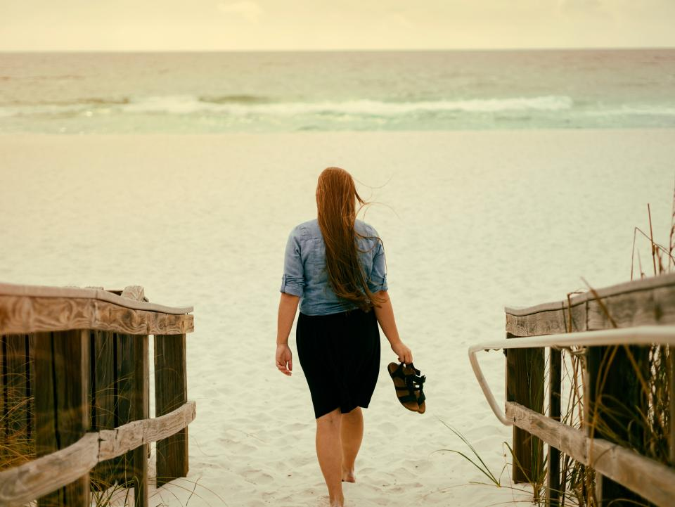 sea ocean water waves nature white sand beach horizon shore people woman walking alone sandal footwear hair grass