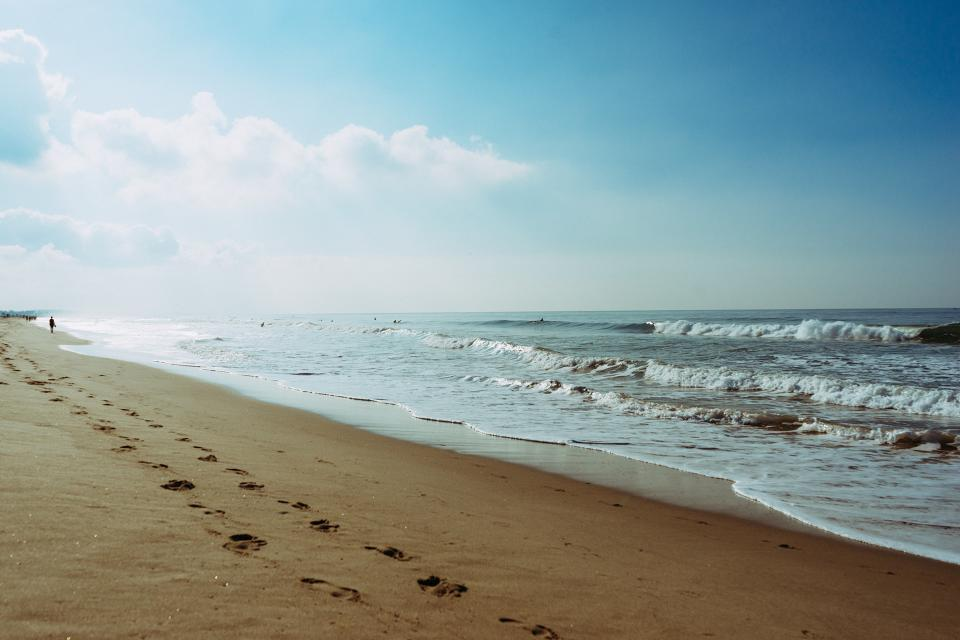 beach sand footprints shore waves ocean sea blue sky